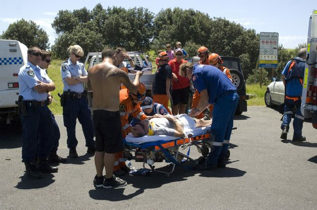Emergency Services attend to Robert Blanch who was caught by surprise by a rogue wave while rock fishing at Boulders Beach near Lennox Head on Sunday.