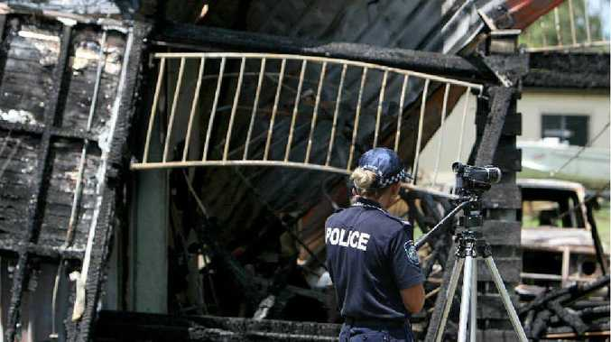 Scenes of crime officer Constable Jodie McClennan films the ruins of the burnt-out house in Kathleen Street, Sarina, yesterday.