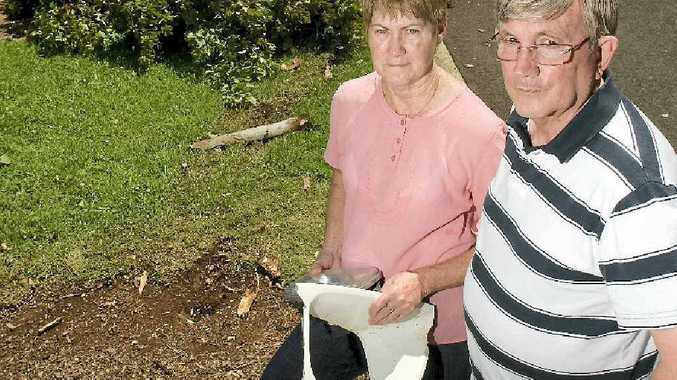 Glenvale residents (from left) Marion and Cliff McMahon are sick of young hoons using the streets as their own private racetracks and (inset) a tree stump wedged under the alleged man's vehicle.