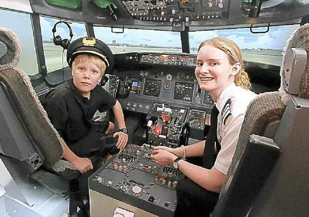 Tyler Boyd at the controls of a Boeing 737 flight simulator with his flying instructor Tess.