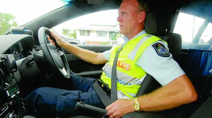Sergeant Gerry Doyle of Mackay traffic branch checks that his seatbelt is on.