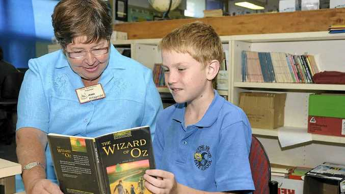 Volunteer Anne Fitzgerald with student Kaid Millers, 10, who is enjoying reading books more since starting at the Exodus Tutorial Centre at the Gladstone South Primary School.