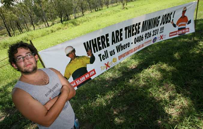 Alex Gonzalez has spent over $5000 getting mining job certifications only to receive hundreds of job application rejections. He asks where are the mining jobs, pictured at the Yeppen Roundabout outside Rockhampton with his banner.