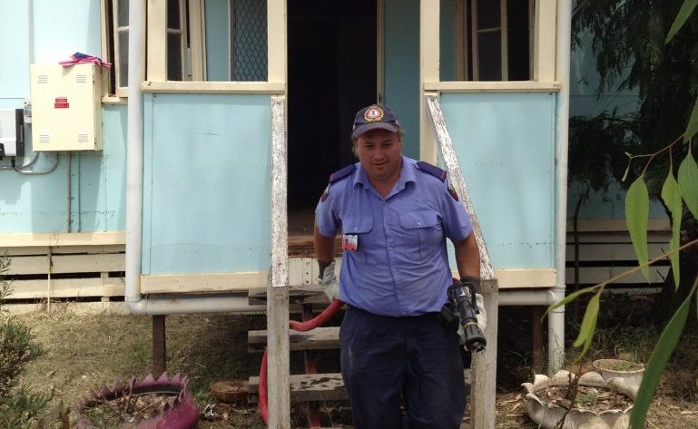 Auxiliary firefighter George Talsma helps to clean out a flood affected home in Mitchell yesterday.