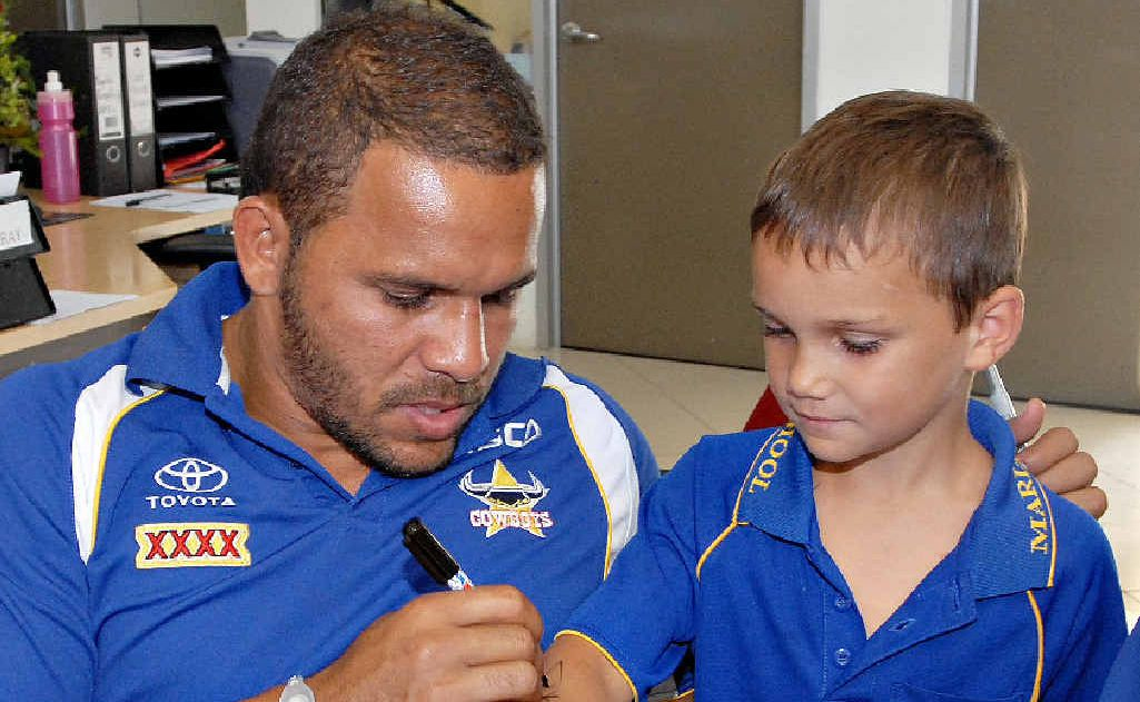 Cowboy Matt Bowen gives Amiri Lagaluga from Marian an autograph to remember on his arm at Mackay Toyota yesterday.