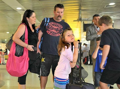 Kristy Clinton, husband Aaron and their children Emma, Matthew and Lachlan arrive at Melbourne Airport after rebooking on Qantas from Brisbane.