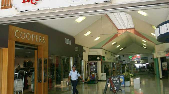 A police officer leaves The Arcade after a woman attempted to rob the newsagency.