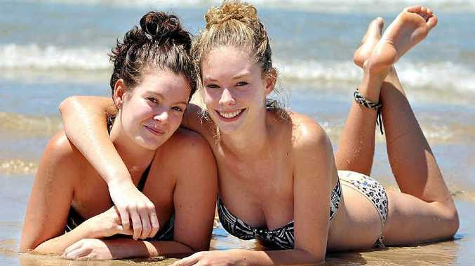 Ange Harford and her younger sister, Shannon, make the most of the fine and warm weather at Maroochydore Beach.