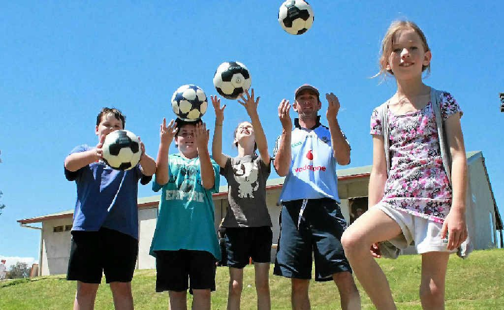 Dylan Lambert, Caine Beggs, Ashleigh and Derek Kane and (front) Madison Kane get ready for the football season.