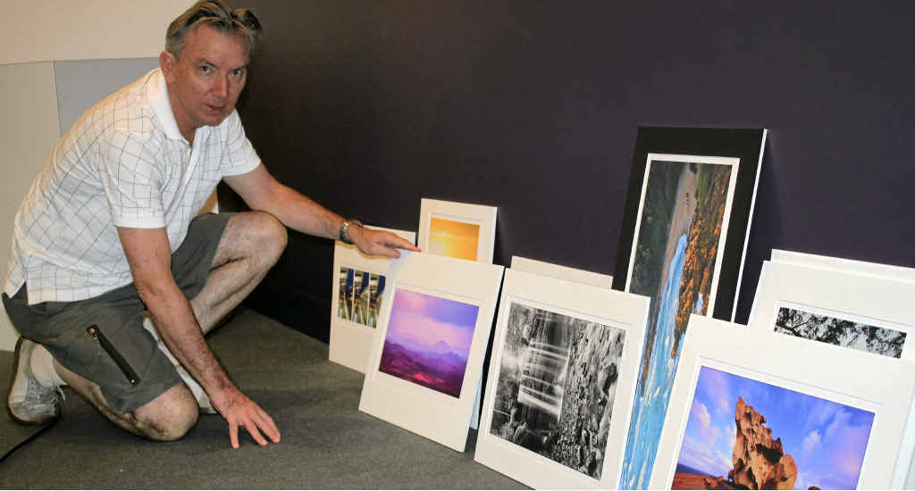 Photographer John Doody sets up his photographs for the Legacy of Light exhibition.