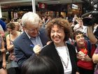 Kevin Rudd signs an autograph for a young fan as he walks through Brisbane's Queen Street Mall.