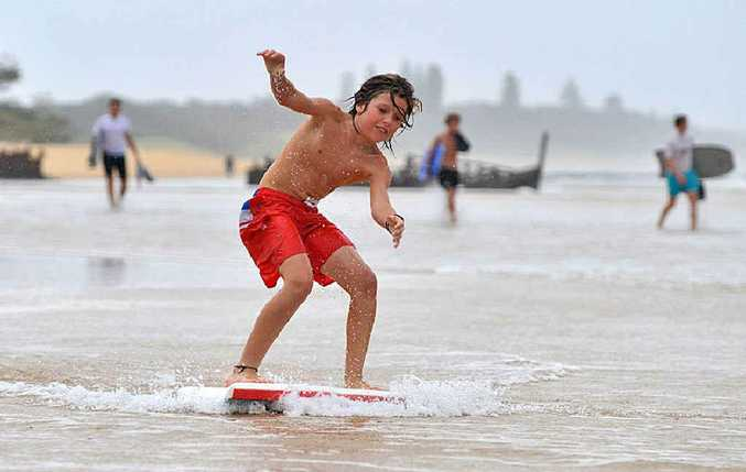 Tallow Wortman, 11, was unfazed by the miserable weather at Dicky Beach, Caloundra.