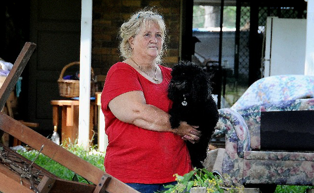 SALVAGE OPERATION: Linda Boyd with her dogs trying to dry out her home after the flood.