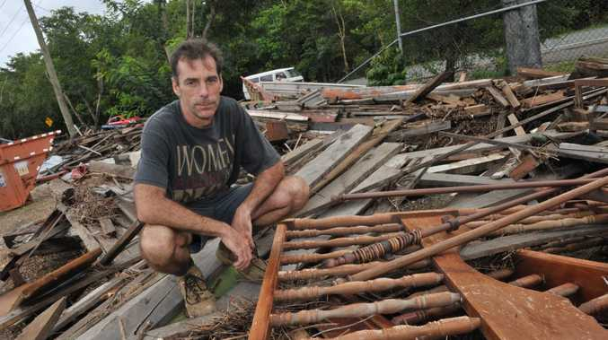 Pomona Re-cycled Timber owner Mark Edwards cleaning up after a flood hit Pomona earlier this year.