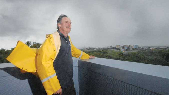 Bureau of Meteorology Mt Bassett weather station manager John McILwham keeps an eye on storm clouds looming over Mackay yesterday.