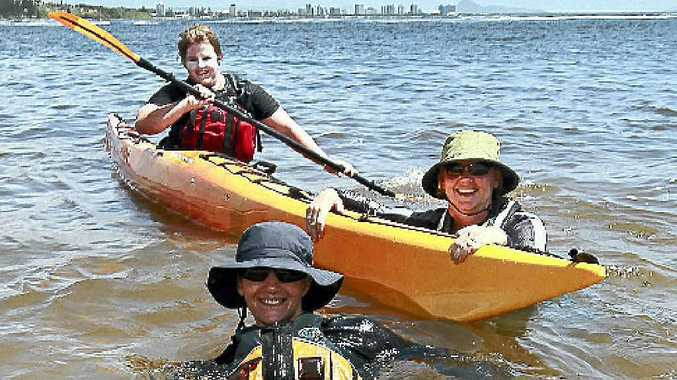 DIVING IN: Having a 'tough day in the office' at Mooloolaba Spit testing their equipment were (clockwise from front) Marjon Deboer, Kati Francis and Allana Bold from Rosco Canoes in Brisbane.