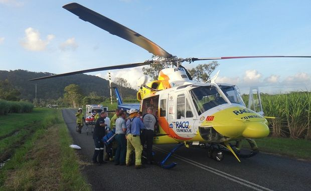 Emergency service workers and RACQ-CQ Rescue crew members prepare to airlift the men to hospital.