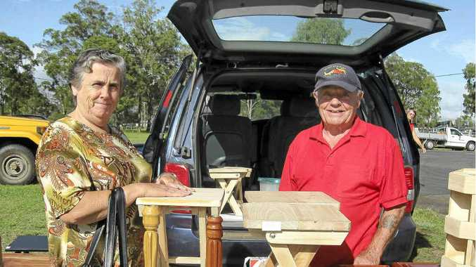 Ted Senior at his market stall showing handcrafted items to local resident Marilyn Dumpleton.