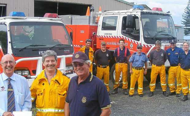 SUPPORT THE FIRIES: Captain Ray Wilton (centre), golf fundraising day organiser Bruce Bevan from the Ballina Rotary Club (right), and Glenn Costello, from Tursa, making a donation to the golf day, watched by some of the Lennox Head Rural Fire Service crew.