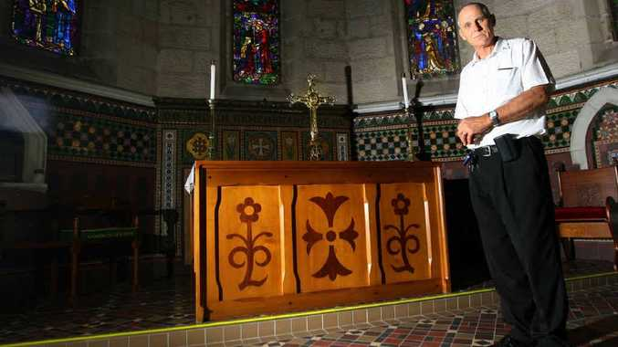 Dean Lindsay Howie stands at an altar in St Paul's Cathedral and a cross a vandal used to cause damage in the building.