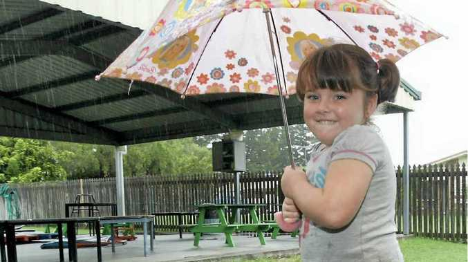 Makayla Denniss, 4, finds a puddle to stand in at Rockhampton's Little Friends Childcare Centre yesterday.
