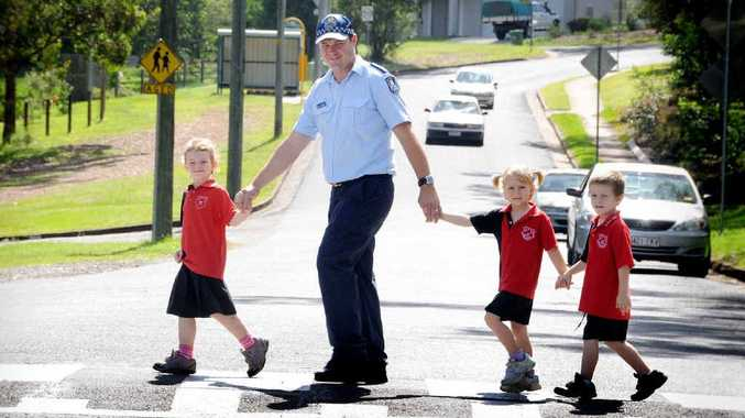 Gympie West primary school's new Adopt-a-Cop, Constable Warwick Mundt, teaches prep students Zoe Parker, Jasmine Lowry and Tristan Bryant how to safely cross the road.