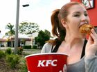 Bec Houterman tries a piece of chicken outside the South Rockhampton KFC store.