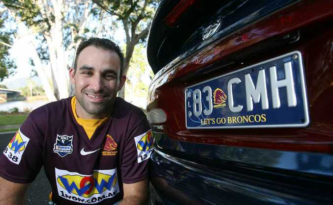 Footy fanatic and Broncos supporter Clint Holloway checks out his new Broncos number plate given to him as an anniversary gift.