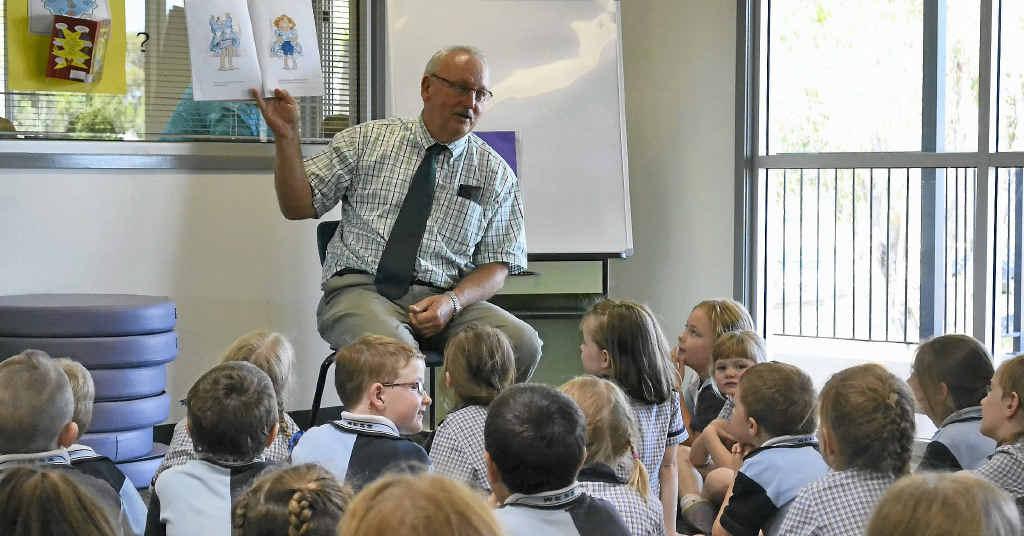 Warwick East State School principal Warren Elder reads to the children.