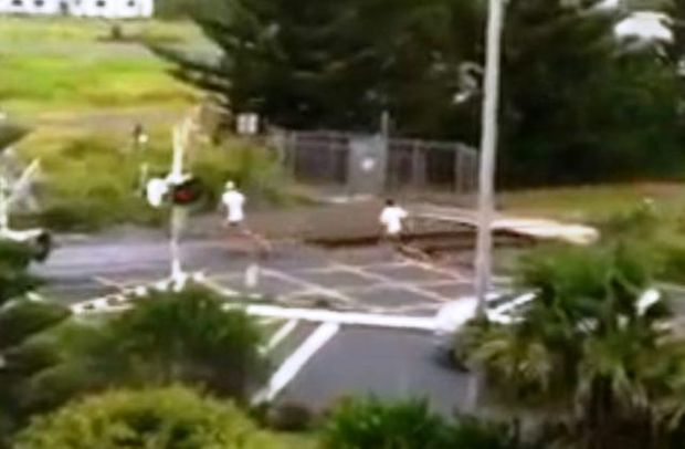 Two youths run through the Jetty train crossing as warning bells sound on Saturday.