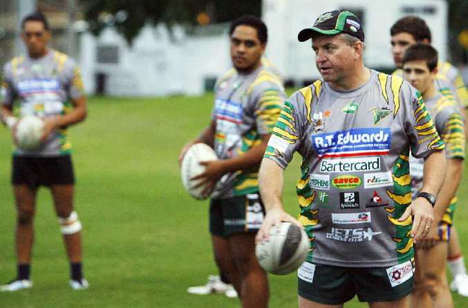 Ipswich Jets Colts coach Mark Bishop issues his instructions at training after players warm up.