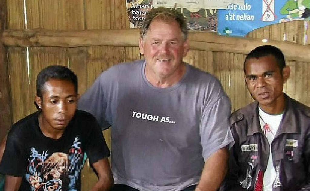 HELPING HAND: Barry Scanlan and the local installation helpers take a break while fitting solar lights into huts in East Timor.