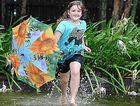 Amelia Kennedy splashes through her flooded backyard.