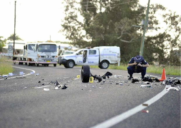 A policeman gathers evidence for a coronial inquest into a fatal accident between a Ford Falcon and a Subaru Liberty on the Bruxner Hwy, 1km north of Casino.