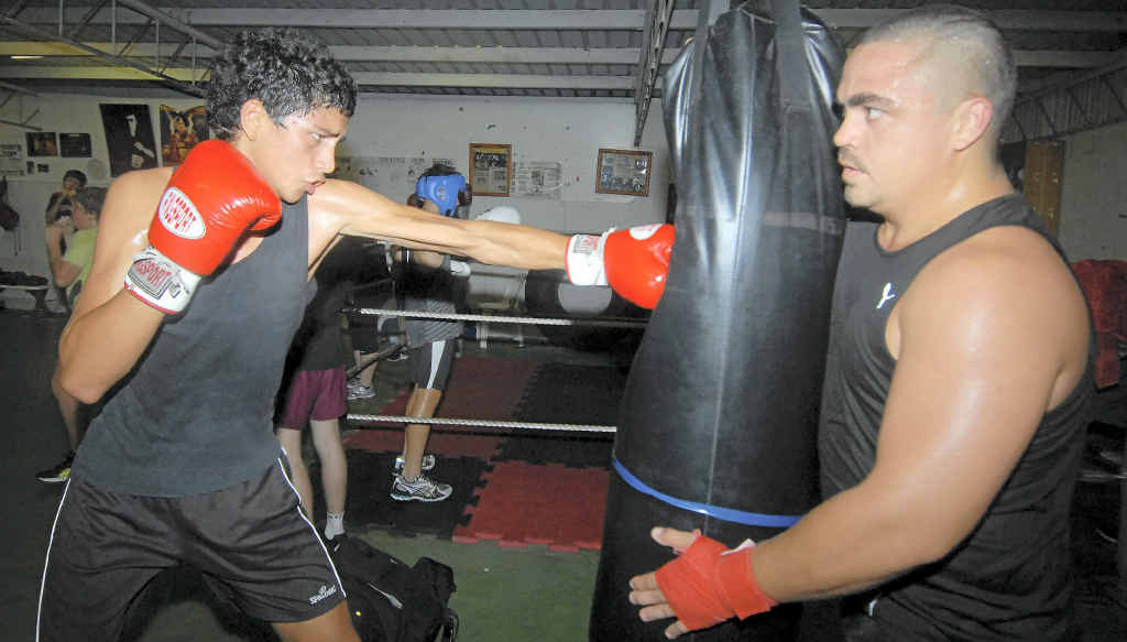 Shaun Pau holds the bag for his son Dallas during a training session. Both are Australian amateur boxing champions.