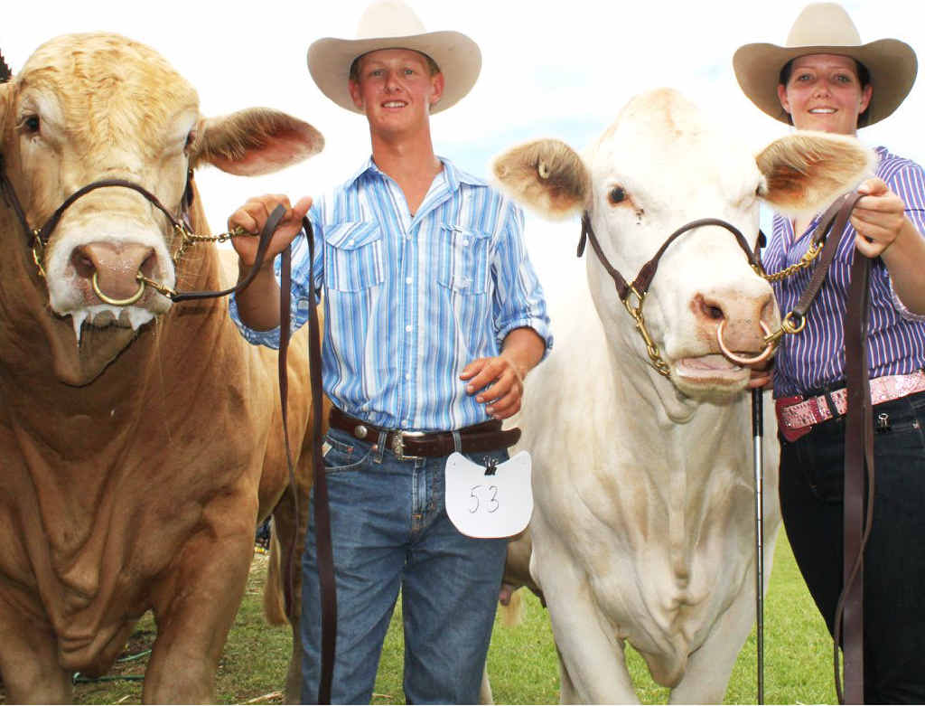 Showing off last year's grand champion bull and cow are Myles and Jayne Newcombe.