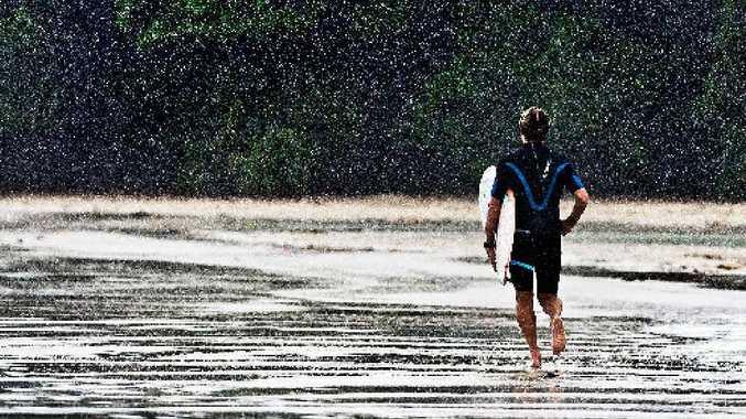 A surfer runs through the rain at Main Beach, Byron Bay.
