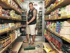 Tony Spinks mops out at his Alexandra Headland food shop.