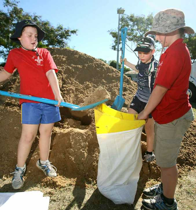 Tyrin Careless and Hunter Brown from the Mt Archer Scouts (front) and Dane Careless from Brothers Junior Rugby League filling sand bags at Rockhampton Showgrounds.