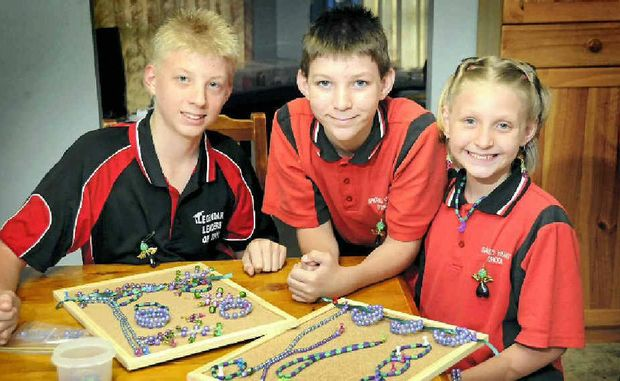Dylan (from left), Curtis and Charlotte Barber with some of their colourful creations they will be selling today. They will send the money they raise to Epilepsy Queensland.