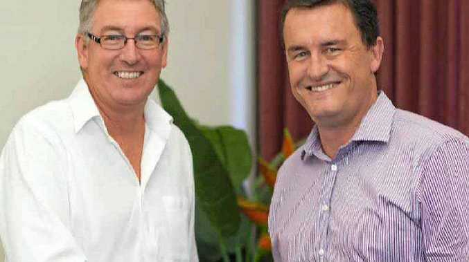 Brown Consulting's Gary Spence and Associates's Graham Scott seal their business merger with a handshake.