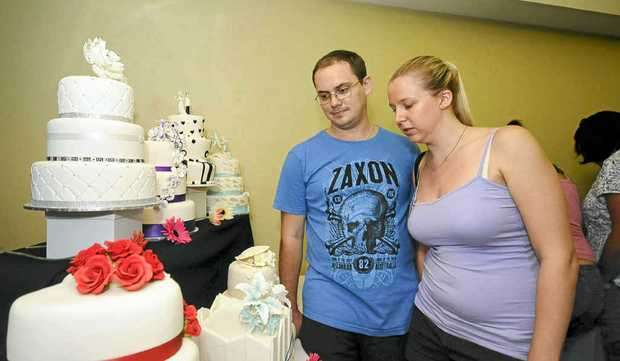 YUM: Brock Collins, with partner Nicole Townsend, both of Ballina, check out the wedding cakes on display.