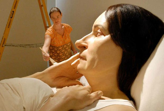 Queensland Art Gallery's modern art sculpture technician Danielle Hastie is overshadowed by the huge Ron Mueck sculpture 'In Bed'.