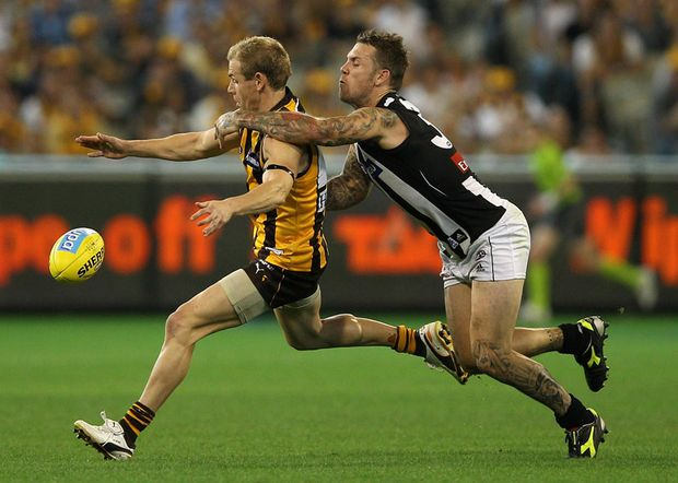 Michael Osborne of the Hawks kicks whilst being tackled by Dane Swan of the Magpies during the round one AFL match between the Hawthorn Hawks and the Collingwood Magpies at the Melbourne Cricket Ground