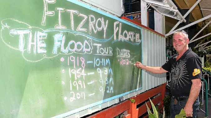 """Fitzroy Float-el owner Tony Higgins updating his flood """"tour dates"""" sign outside his Depot Hill pub after the flood peaked."""