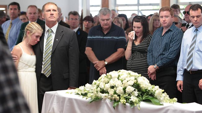 Matthew Barclay's younger sister Lauren, 12, is comforted by her dad Stephen at the funeral of the promising Maroochydore lifesaver. Photo: Cade Mooney/ Sunshine Coast Daily
