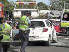 Crews attend to a woman after a crash near Bundaberg Hospital.
