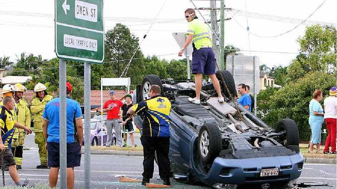 A car that flipped onto its roof during an accident at Raceview yesterday is prepared for removal.