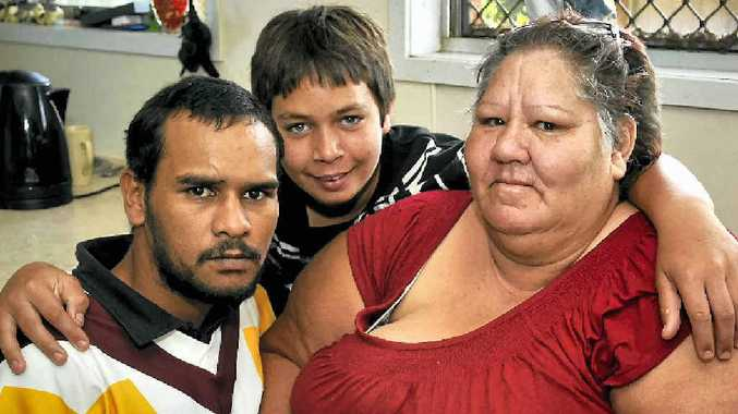 """Mrs Kim """"Nanna"""" McCarthy gets a loving hug from grandson Michael Hearn (at back) and nephew Jarret Rose at Mrs McCarthy's Rockville home where she found another grandson and his mates had stored a large booty of stolen goods."""