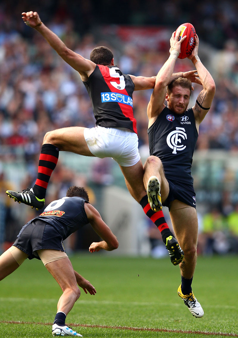 Zach Tuohy of the Blues marks under pressure from Brent Stanton of the Bombers during the round four AFL match between the Carlton Blues and the Essendon Bombers at Melbourne Cricket Ground